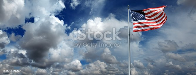 Conceptual image of waving American flag hanged at tall pole over cloudy sky