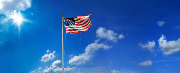 waving American flag at tall flagpole over clear blue sky stock photo