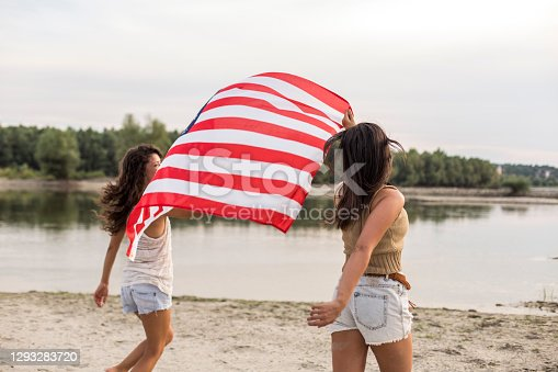 Rear view of two cheerful young women running at the beach and waving with a big American flag while celebrating Independence day.