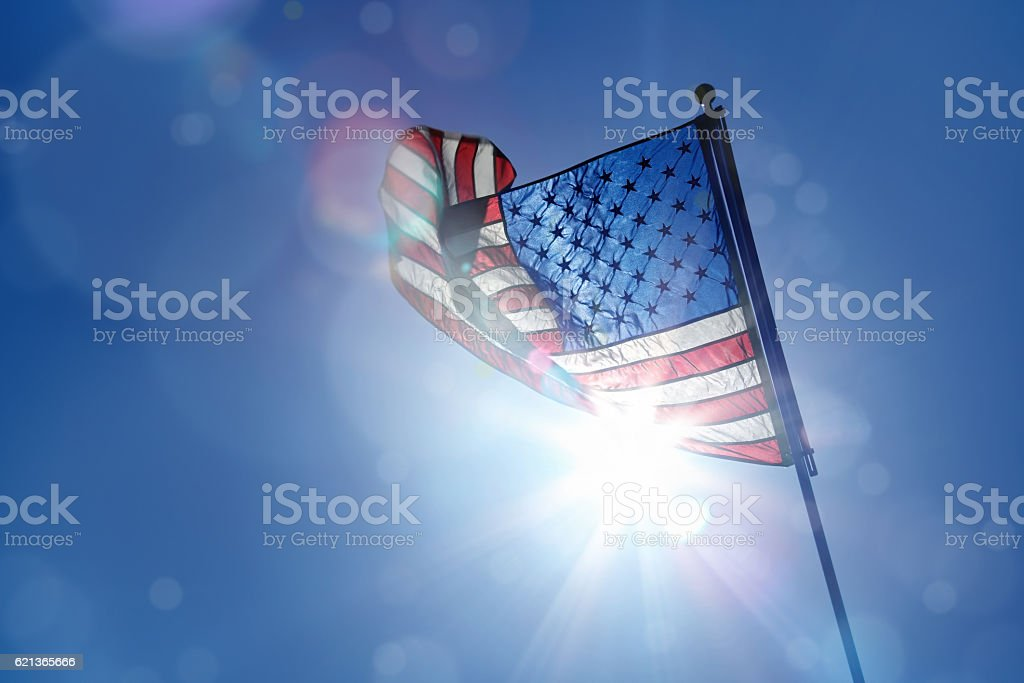 Waving American flag over sun stock photo