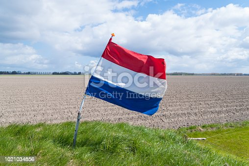 waving dutch flag in a typical flat agricultural landscape