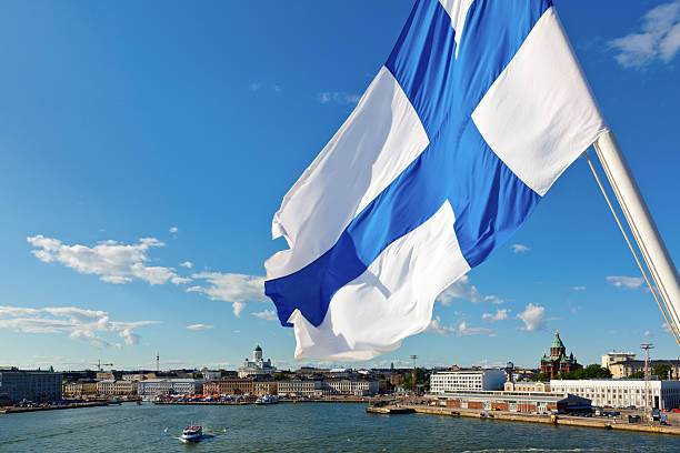 waving finnish flag - finland stock pictures, royalty-free photos & images