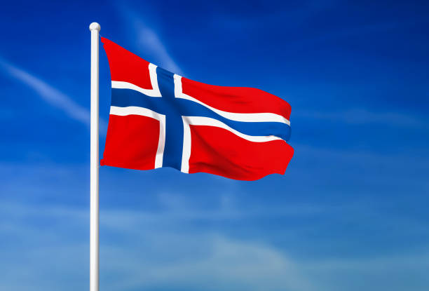 Waving flag of Norway on the blue sky background - fotografia de stock