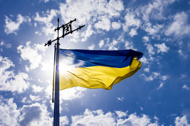 Waving flag of Ukraine against the blue sky in front of the sun. stock photo