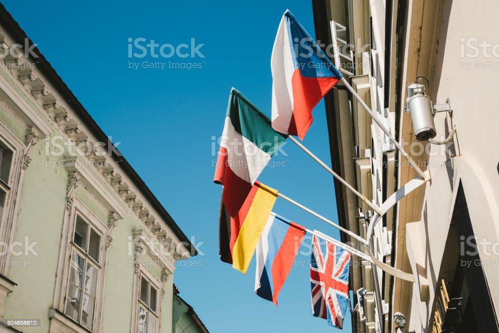 Agitando banderas frente edificio europeo en Praga, Checo - foto de stock