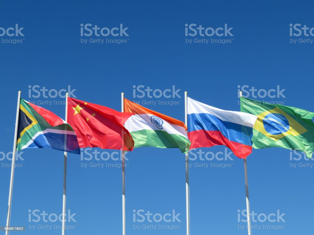 Waving flags of the BRICS countries against the blue sky stock photo
