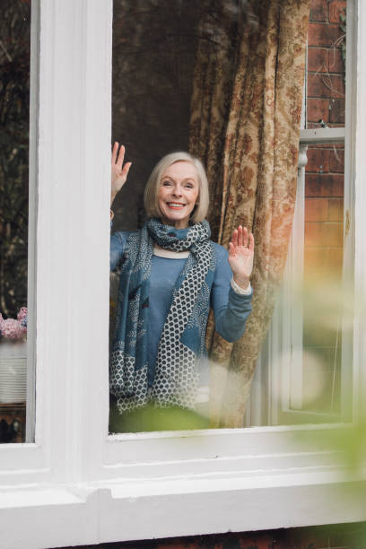 waving goodbye aan familie - raam bezoek stockfoto's en -beelden