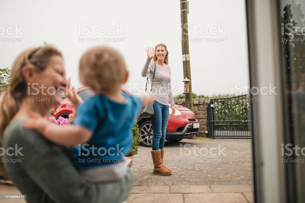 Waving Goodbye To Her Mother And Son stock photo