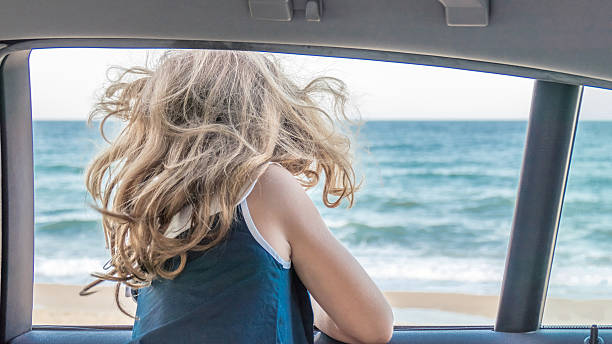 Waving hair of cute girl showing from car window stock photo