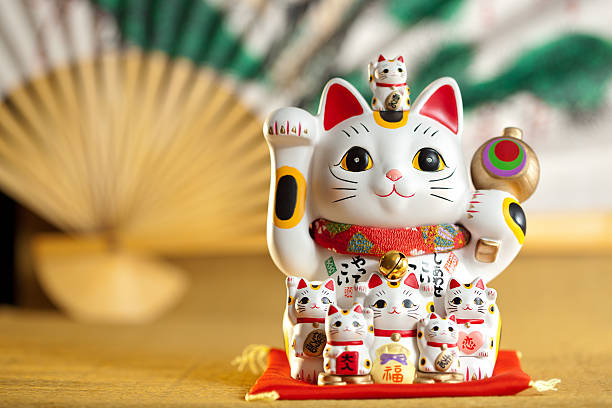 Waving lucky Japanese cat with a fan in the background stock photo