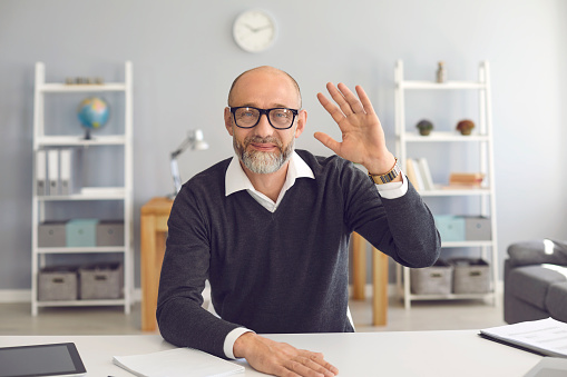 Hand waving old businessman smiling looking at the camera video call web camera gadget sitting in the apartment. A mated man greets a partner on a laptop monitor. Remote communication people video conference.