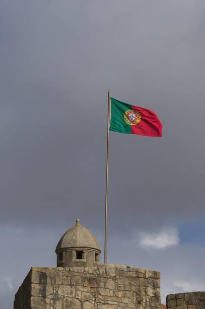 waving portugese flag - rain clouds porto portugal imagens e fotografias de stock