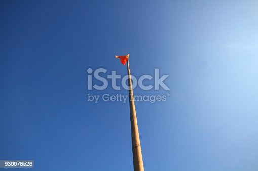 istock Waving red flag on blue sky background 930078526