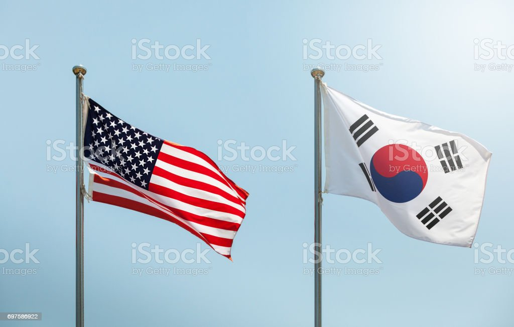 waving the American flag, the Star-Spangled Banner, the Stars and Stripes and south korean flag on blue sky, korean and us alliance, us and korean alliance stock photo