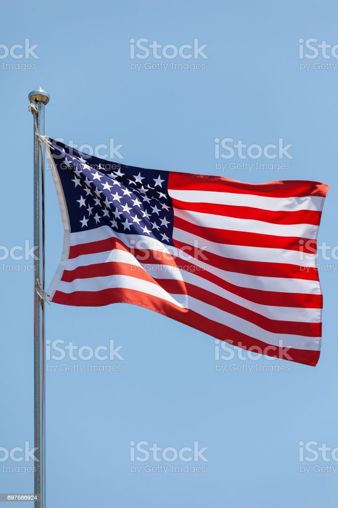 waving the American flag, the Star-Spangled Banner, the Stars and Stripes on blue sky stock photo