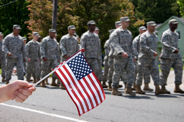 Waving the Flag for soldiers A childs hand holds an American Flag up while American soldiers march by in a parade. military parade stock pictures, royalty-free photos & images