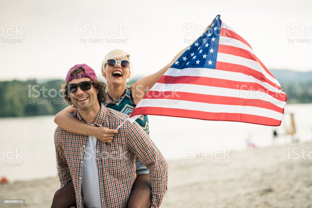 Waving US flag in the hands of American youth stock photo