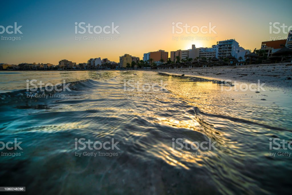 Wavy curves of sea is covered in golden sunset light. Sea at sunset...