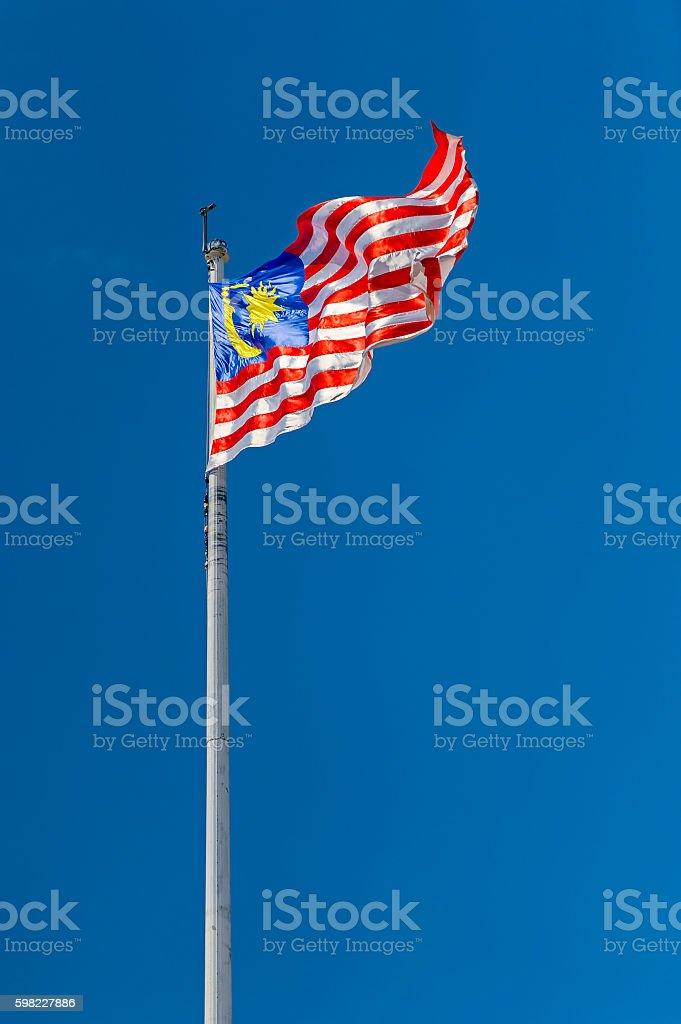 Wavy Malaysian flag on clear deep blue sky foto royalty-free