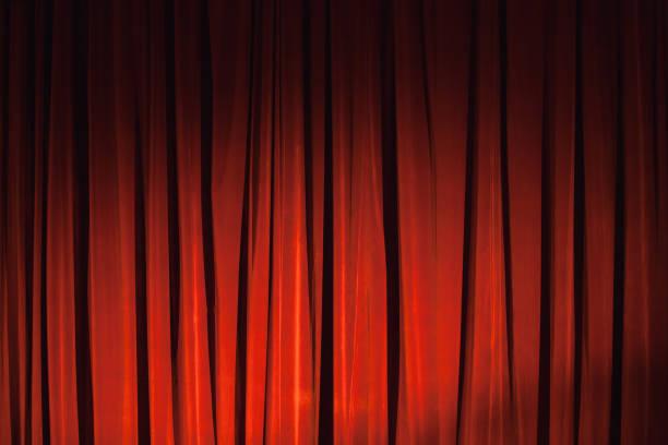 wavy red velvet curtain with spot illumination - sipario foto e immagini stock