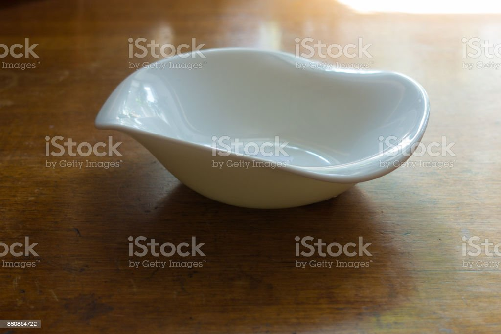 Wavy rimmed porcelain bowl on wooden table stock photo