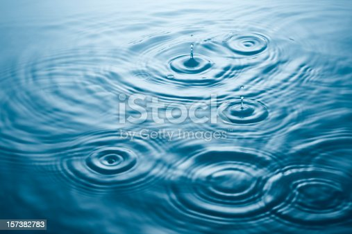 Multiple drips and ripples on bright blue calm water