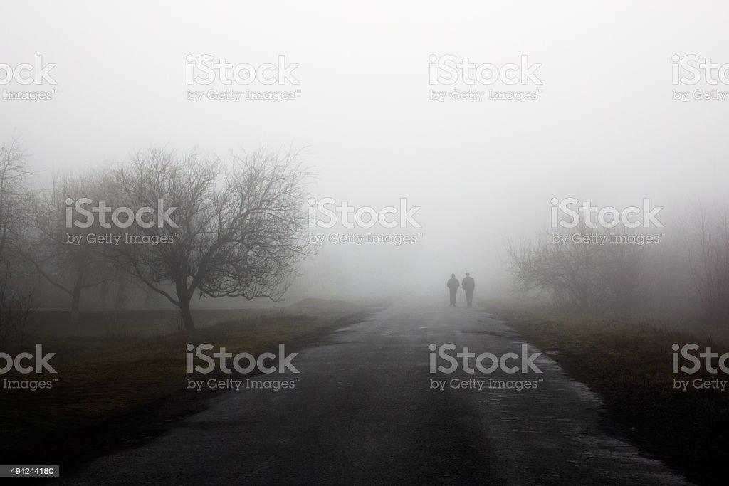 Wayfarers in fog stock photo
