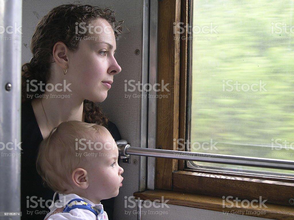wayfarers peer into window of train mother with son stock photo