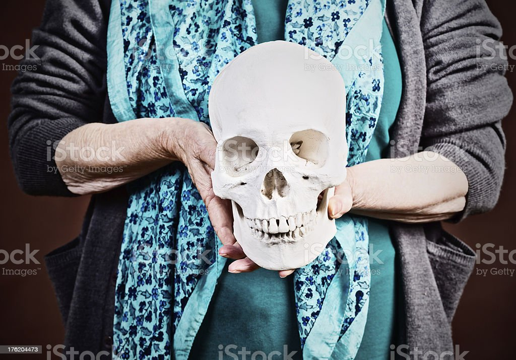 We all have to go sometime! Old woman holds skull stock photo