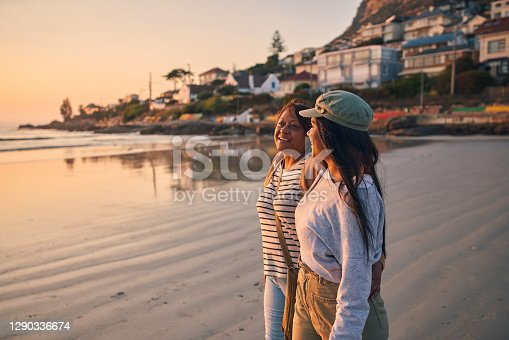 Shot of a mature woman and her adult daughter taking a walk on the beach