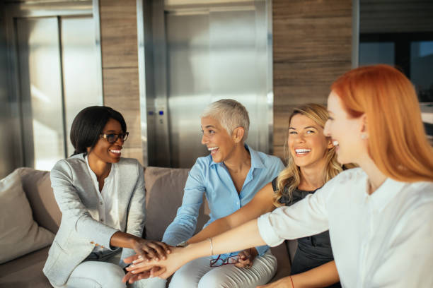 We are all together Portrait of successful business team putting hands together indoors. age contrast stock pictures, royalty-free photos & images