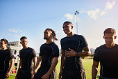 Cropped shot of a diverse group of sportsmen standing together before playing rugby during the day