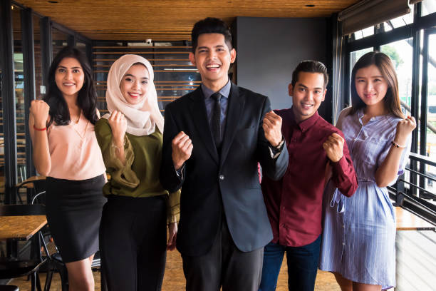 We are empowered to lead Multi-ethnic group of business team standing tall and togetherness as leaders of the business world business Malaysia stock pictures, royalty-free photos & images