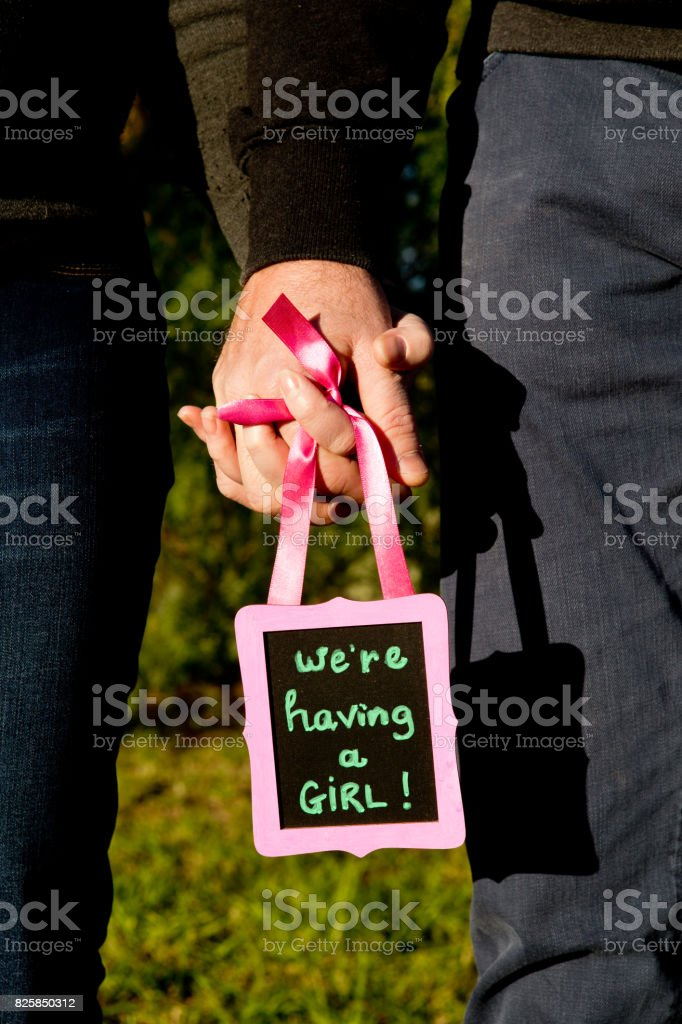 We are having a Girl - announcement message for expecting a new baby girl - holding hands with handwritten text on blackboard stock photo