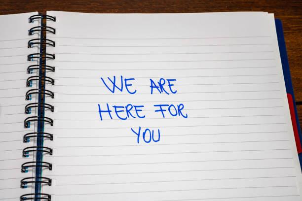 vi är här för dig handskrift text på papper, på kontoret dagordning. kopiera utrymme. - emotionellt stöd bildbanksfoton och bilder