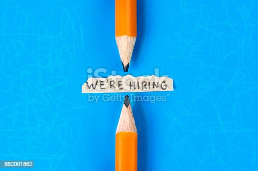 477419728istockphoto We are hiring message between two pencils on blue textured background. Job search concept. 882001862