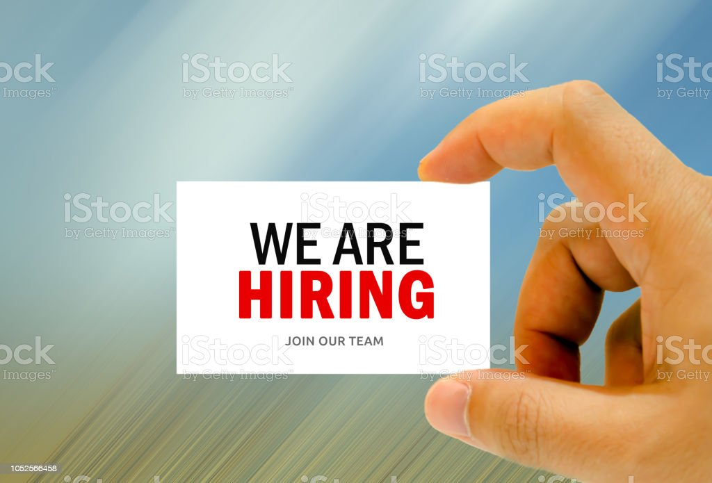 we are hiring written on man hand business card stock photo