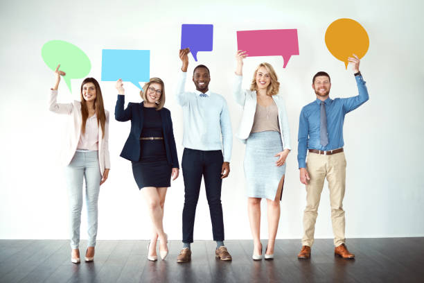 We are loud and proud! Shot of a group of work colleagues standing next to each other while holding speech bubbles against a white background speech bubble stock pictures, royalty-free photos & images