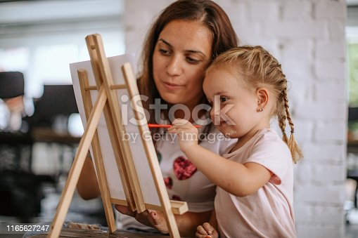 Mother teaching her daughter how to paint on canvas