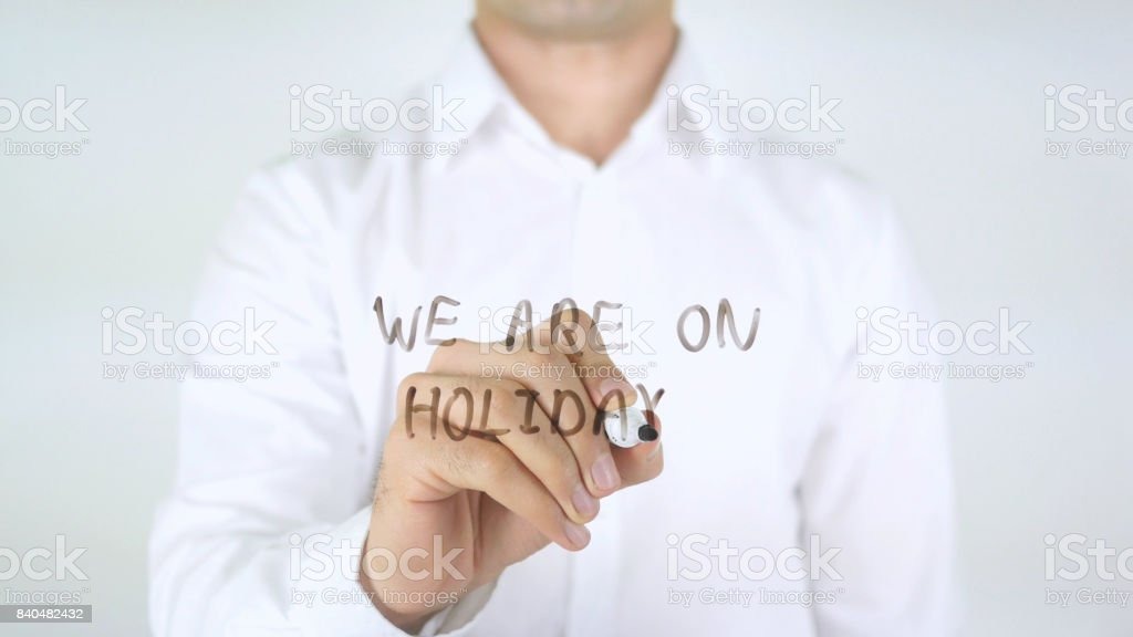We Are On Holidays, Man Writing on Glass stock photo
