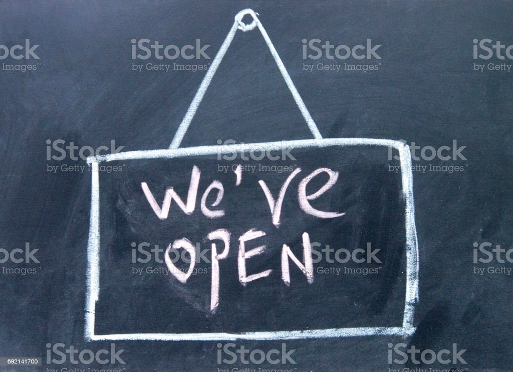 we are open  sign drawn with chalk on blackboard stock photo