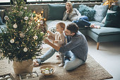 Family with one child decorating Christmas tree. They are happy and enjoy in preparation for holidays.