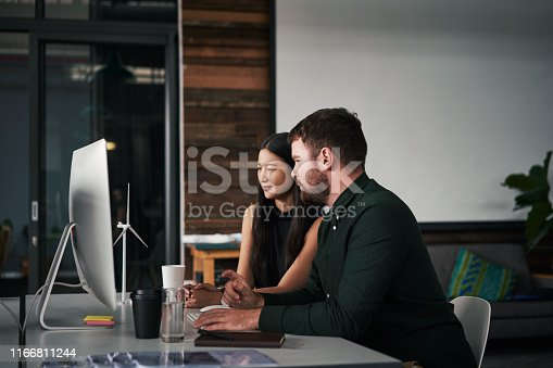 Shot of two young businesspeople working on a computer together inside an office