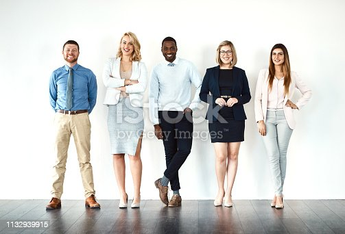 Portrait of a group of work colleagues standing in a line while using their wireless devices against a white background