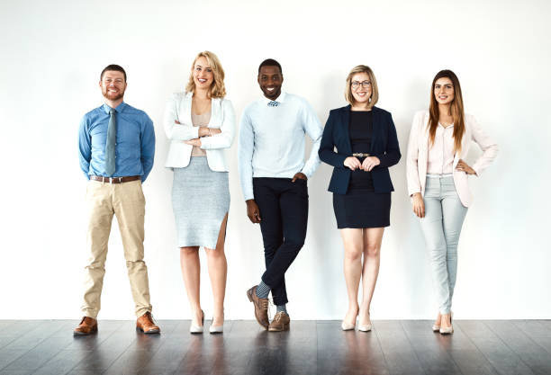We call the shots Portrait of a group of work colleagues standing in a line while using their wireless devices against a white background people in a row stock pictures, royalty-free photos & images