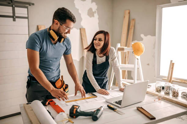 We can do it together Woman analyzing blueprint for her new home interior home improvement stock pictures, royalty-free photos & images
