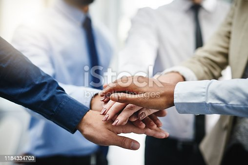 Cropped shot of an unrecognizable group of businesspeople standing in the office together with their hands stacked