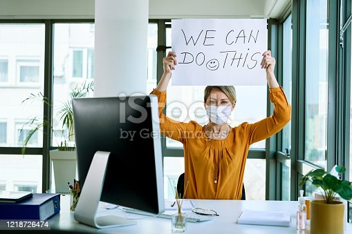 Businesswoman holding placard with we can do this text as support during virus epidemic.