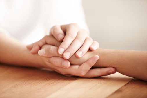 Hands holding one another on a table in prayer