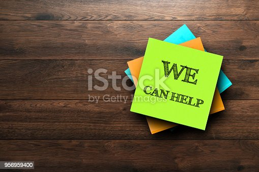 istock We Can Help, the phrase is written on multi-colored stickers, on a brown wooden background. Business concept, strategy, plan, planning. 956959400